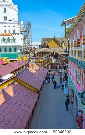 MOSCOW RUSSIA - MAY 10 2015: The covered stalls of Vernissage Market in Izmailovo with the timbered building of art workshop in front on May 10 in Moscow.