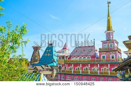 The colorful fairy tale mansion with golden spire rooster weathervane and painted facade serves as hotel and craft center in Izmailovsky Market the Russian style entertainment and trade center Moscow Russia.