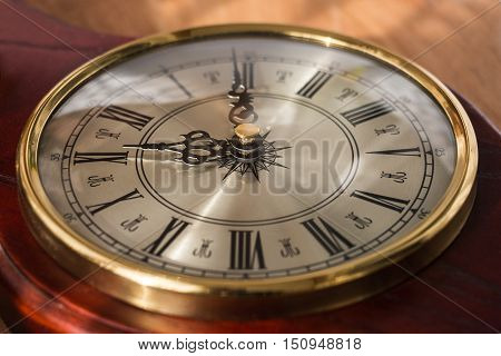 Antique clock with Roman numerals and a beautiful face. Watches are decorated with noble wood