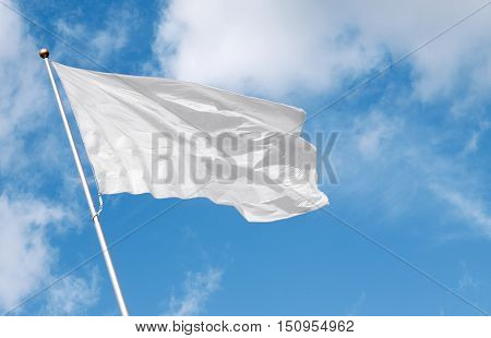 White flag waving in the wind against cloudy sky. Perfect mockup to add any logo symbol or sign