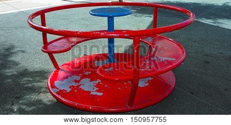 red children's carousel in the yard in the summer metal roundabout park