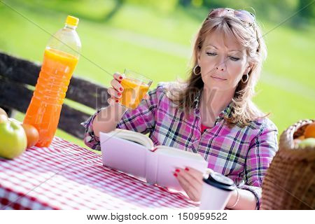 Mid adult woman sitting in park and reading a book on picnic