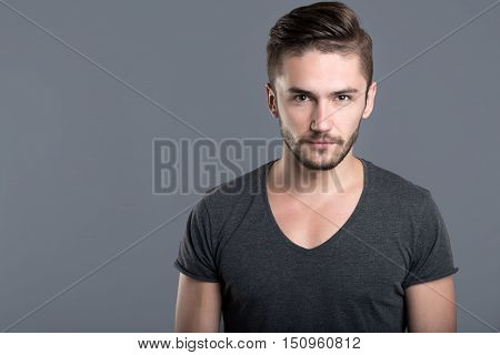 Feeling of anger. Annoyed bearded young man standing against grey background