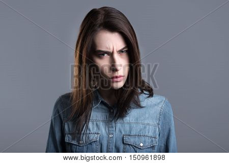Anger. Furious young woman standing against grey background and looking at you