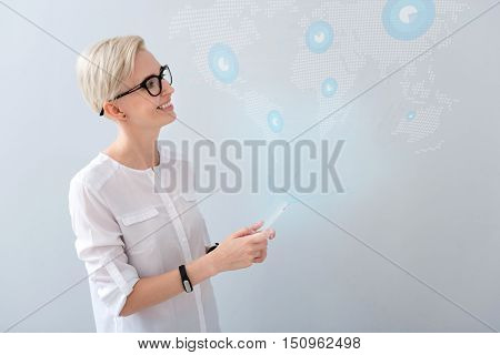 Worlwide technologies. Positive beautiful woman smiling and looking aside while standing isolated on grey background