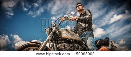Biker man wearing a leather jacket and sunglasses sitting on his motorcycle.