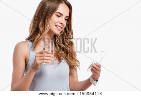 Active life. Joyful delighted smiling young woman drinking water and using cell phone while standing isolated on white background