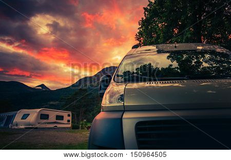 Scenic RV Park Camping During Beautiful Summer Sunset. Motorhome and Travel Trailers in the Background.