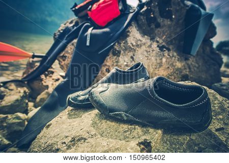 Water Sports Drying Wetsuit and Aqua Shoes on the Large Boulder. Water Sports Equipment.