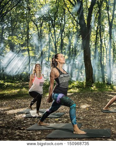 Group of youngsters keep in shape exercising in sunlight woods