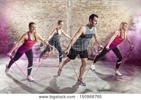 Cheerful people doing mix of modern workout,  stretching and cardio exercise