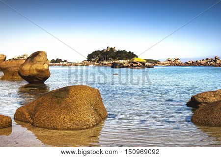 Ploumanach ock and bay beach in morning. Toned. Pink granite coast Perros Guirec Brittany France. Long exposure.