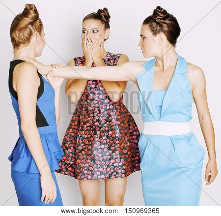 three elegant fashion woman fighting on white background, bright dresses evil faces, people quarrel concept
