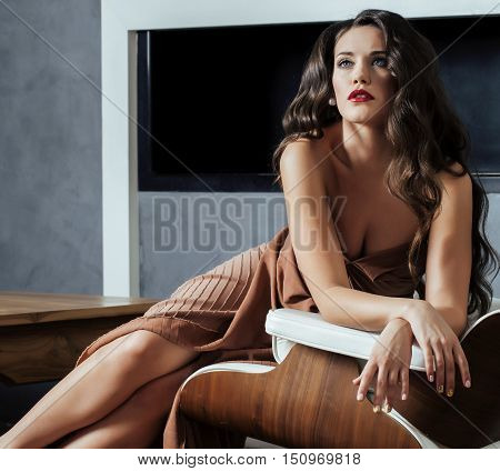 beauty yong brunette woman sitting near fireplace at home, winter warm evening in interior, waiting to celebrate womans day
