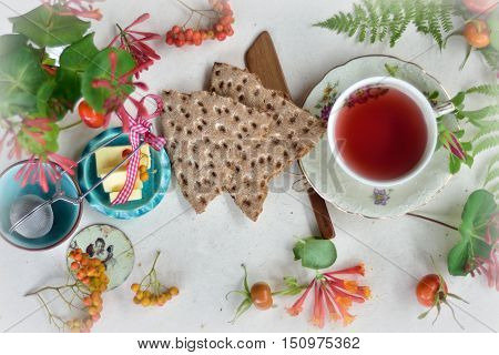 A healthy flatlay with tea, hard bread and butter surrounded with things from the nature.