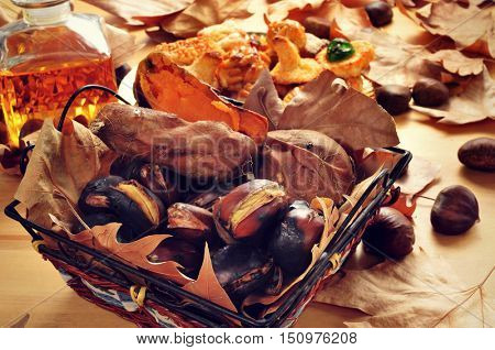 closeup of some roasted chestnuts and sweet potatoes in a basket, and a plate with Catalan panellets, and a glass bottle with sweet wine, typical snack in All Saints Day in Catalonia, Spain