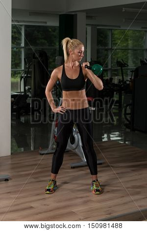 Fitness Woman Using Kettlebells Inside Gym