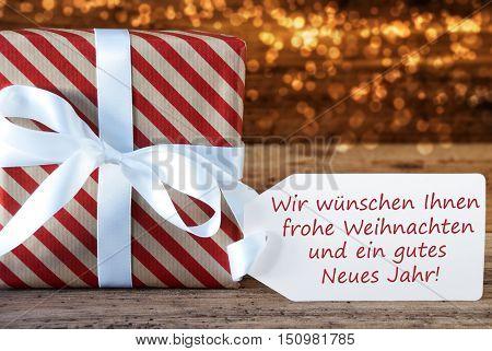 German Text Wir Wuenschen Ihnen Frohe Weihnachten Und Ein Gutes Neues Jahr Means Merry Christmas And Happy New Year. Macro Of Christmas Gift Or Present On Atmospheric Wooden Background.