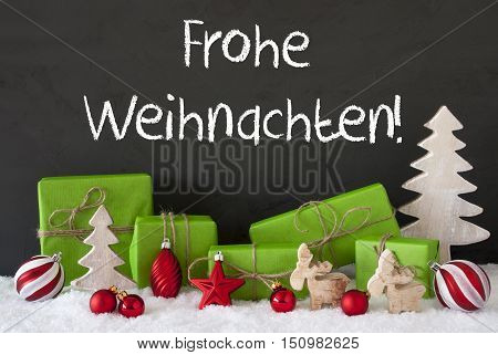 German Text Frohe Weihnachten Means Merry Christmas. Green Gifts Or Presents With Christmas Decoration Like Tree, Moose Or Red Christmas Tree Ball. Black Cement Wall As Background With Snow.