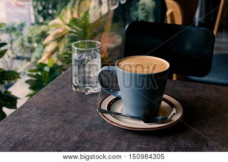 hot fresh coffee blue cup on table chair and glass of water surrounding tree / hot fresh coffee blue cup
