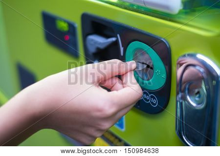 Hand inserting coins into vending machine. soft focus.