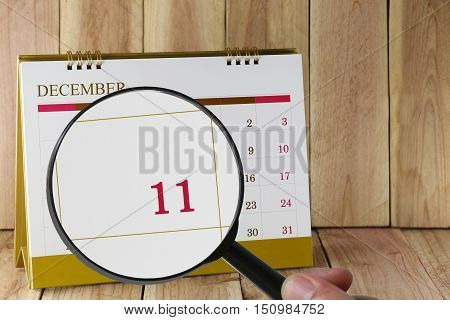 Magnifying glass in hand on calendar you can look Eleventh date of monthFocus number eleven in DecemberConcept in business and meetings.