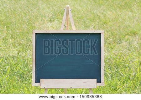 empty chalkboard with wooden easel on green field background