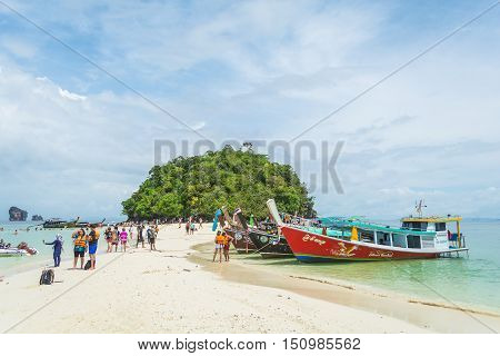KRABI THAILAND - JUNE 1 2016: Unidentified tourists walk around Thale Waek with colorful long-tailed boats in Krabi Thailand.