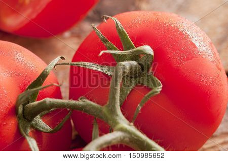 Detail close up on very ripe red tomatoes with green stems and moisture on the skin