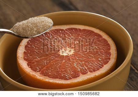 Close up of spoon with full of brown sugar being held above a freshly cut grapefruit half in bowl