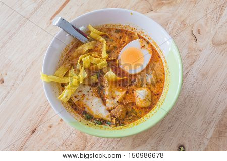 Spicy Thai Tomyum noodle with pork vegetable egg and balls in a ceremic bowl on a wooden table.