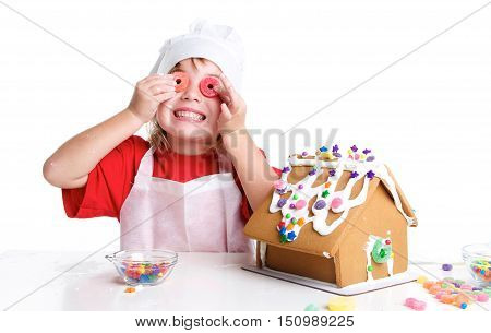 Little Girl Decorating a Gingerbread House for Christmas.  She has round candy in front of her eyes with a silly face