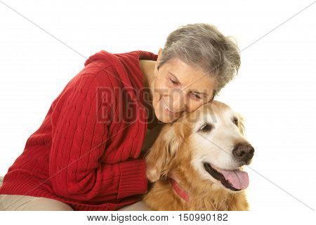 Elderly Woman happy with her pet dog golden retriever.  She is giving him a hug.  Shot on a white background.