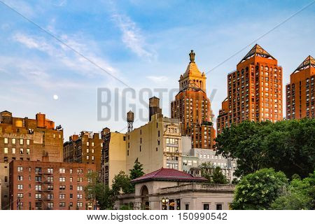 Moon rising in the sky above Union Square Park at sunset in Manhattan New York City