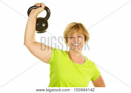 Middle Age Woman Exercising with Weights on a White Background.  She is using a kettle bell to do a military press