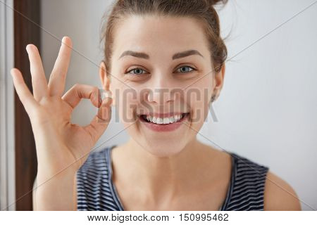 Young European Brunette Female Showing Ok-gesture With Her Fingers. Happy Woman In Striped Top Smili