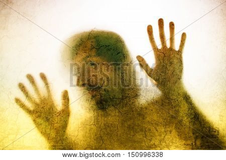 Trapped man concept with back lit silhouette of hands behind matte glass useful as illustrative image for human trafficking prostitution imprisonment mental illness captivity depression.