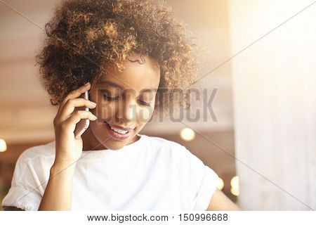 Attractive Fashionable Dark-skinned Girl With Afro Haircut Wearing White T-shirt Having Phone Conver