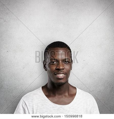 Portrait Of Handsome Good-looking African Man Looking At Camera With Pleased Expression. Black Male