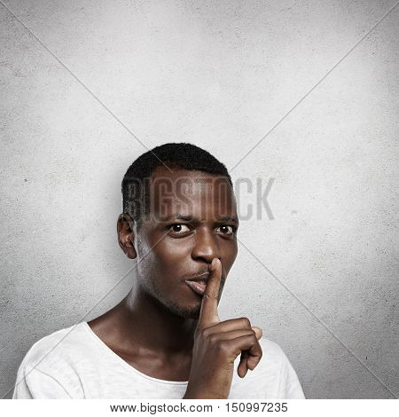 Attractive Dark-skinned Man With Mysterious Look, Holding Finger On His Lips, Asking To Keep In Secr