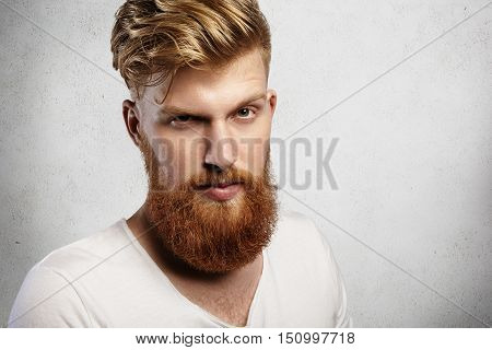 Portrait Of Young Handsome Hipster With Thick Red Beard And Mustache Looking At Camera With Confiden