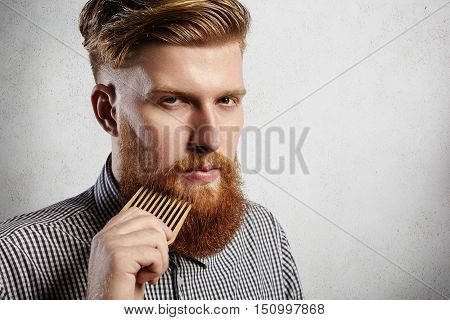 Portrait Of Young Attractive Redhead Hipster Male With Serious And Confident Look, Holding Wooden Co