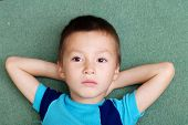thoughtful child portrait lying on crossed arms poster