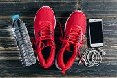 Fitness concept Essential running item Overhead view of running shoe water smartphone and earphone poster