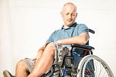 Disabled man with handicap on wheelchair in depression moment - Disability concept with powerless unhelped person sitting alone on wheel chair - Social issues with invalid guy on difficulties poster