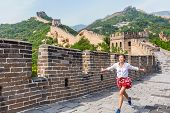 Happy cheerful joyful tourist woman at Great Wall of China having fun on travel smiling laughing and dancing during vacation trip in Asia. Girl visiting and sightseeing Chinese destination in Badaling poster