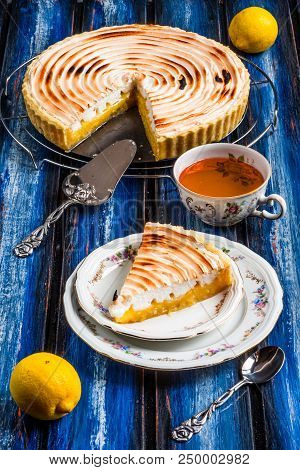 Lemon Tart With Meringue Topping On A Wooden Blue Table Board