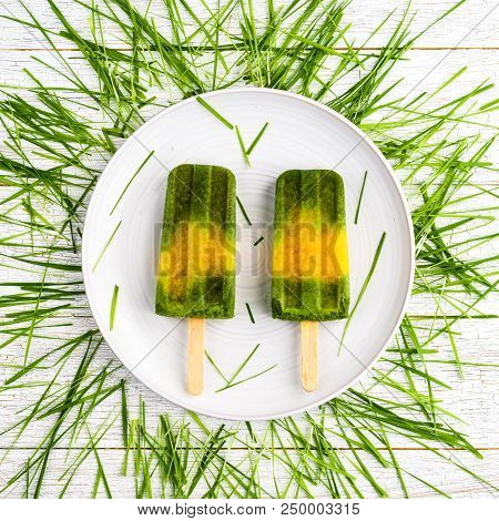 Wheatgrass And Orange Popsicles On A White Plate