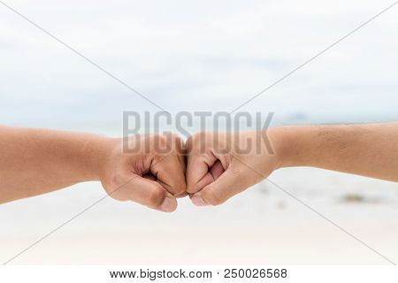 Men Hands Fist Bumping Together On Blurred Sea And Sky Background. Friendship Day Concept.