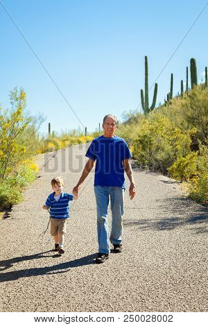 A Grandfather And His Young Grandson Hike Downhill, Holding Hands, On A Sunny Day In The Tucson, Ari